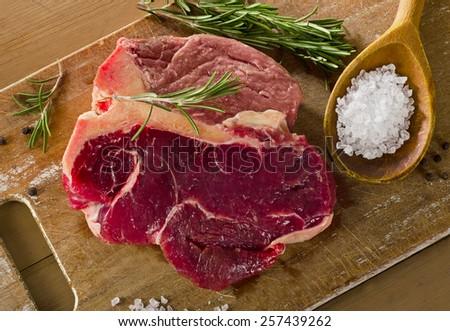Raw beef t-bone steak on  old wooden board. - stock photo