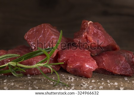 Raw beef with spices on wood background - stock photo