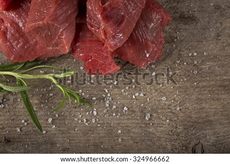 Raw beef with spices on wood background with copy space - stock photo