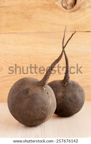 Raw black radish on wooden background - stock photo