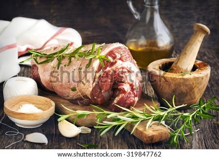 Raw boneless lamb leg with garlic and rosemary on wooden background - stock photo