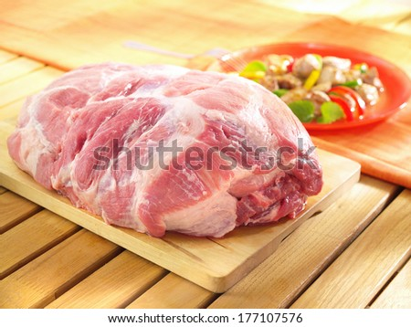 Raw boneless shoulder square cut on a wooden cutting board and wooden table.