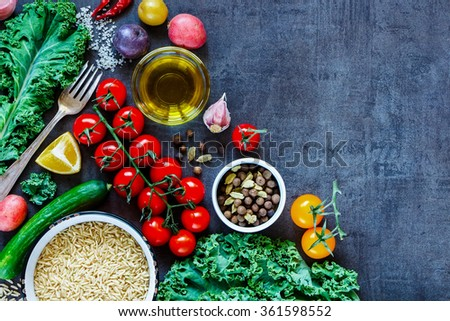 Raw brown rice with fresh delicious vegetables and ingredients for tasty cooking on vintage dark background, border. Top view. Diet or Sports nutrition concept. - stock photo