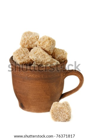 Raw cane brown sugar cubes in a ceramic cup. - stock photo