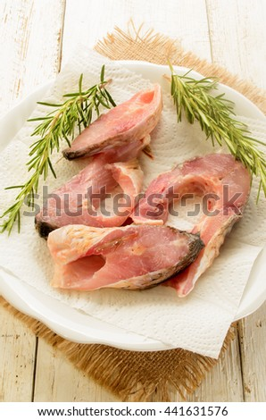 raw carp steak with paper kitchen towel and rosemary on a white plate - stock photo