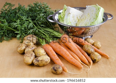 Raw carrot, new potatoes and cabbage vegetable on a table ready for soup.  - stock photo