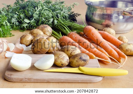 Raw carrot, new potatoes and onion vegetable on a table ready for soup.  - stock photo