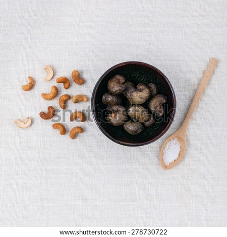 Raw cashews nut in the bowl with salt on white table. - stock photo