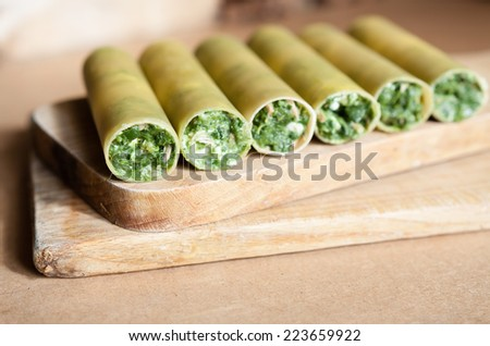 Raw cenelloni with spinach and melted mozzarella cheese as  vegan or vegetarian meal on wooden board - stock photo