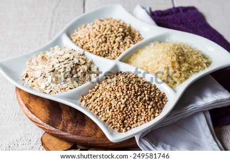 raw cereals, buckwheat, oats, pearl barley, white rice, garnish on a white plate