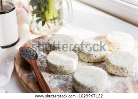 raw cheese cakes with poppy seeds on a wooden surface. with ingredients