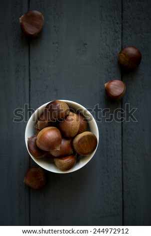 Raw chestnuts in a white bowl -top view - stock photo