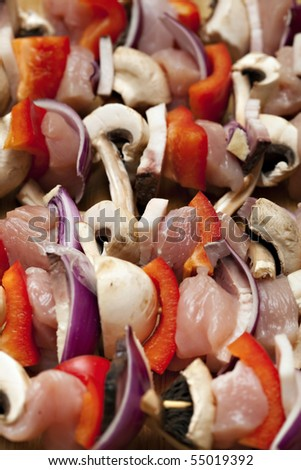 Raw chicken and vegetable kabobs. - stock photo