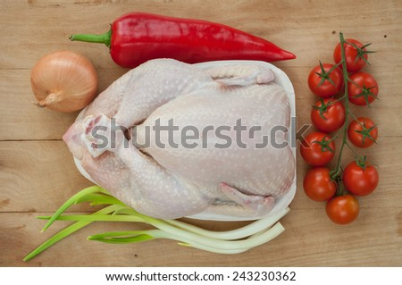 Raw chicken and vegetables on wooden table