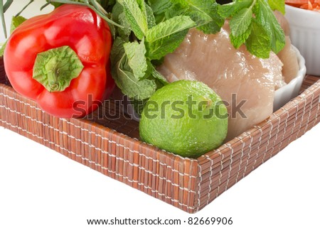 Raw chicken breast and vegetables on a brown tray.