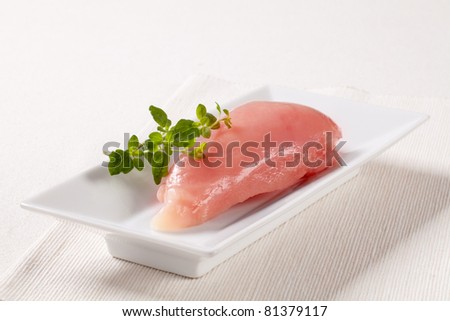 Raw chicken breast in a white porcelain dish - stock photo