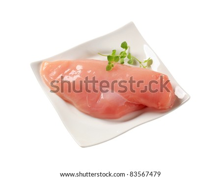 Raw chicken breast on a white plate - stock photo