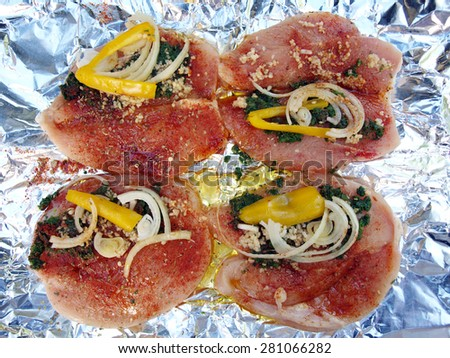 raw chicken breast stuffed with spinach, onion and pepper on foil in preparation for being cooked - stock photo