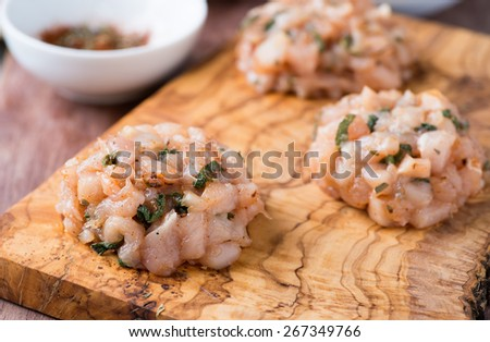 Raw chicken cutlets with herbs on olive wood background, selective focus