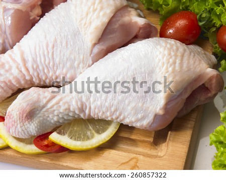 Raw chicken drumstick on the chopping board - stock photo