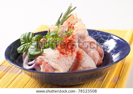 Raw chicken drumsticks seasoned with red paprika - stock photo