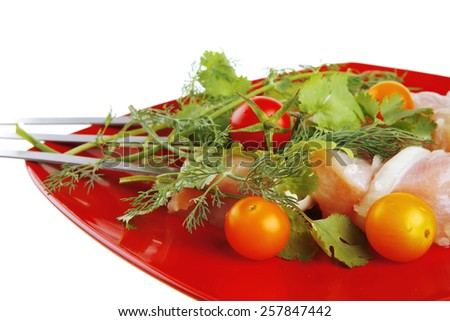 raw  chicken kebabs served with cherry and greenery - stock photo