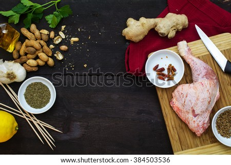 raw chicken leg with ingredients on a dark wooden table, view from above, cooking Asian meat skewers with satay peanut sauce - stock photo