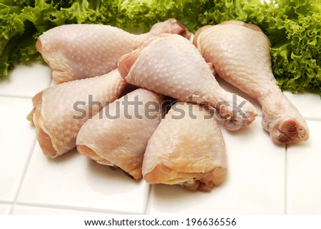 Raw chicken legs garnished with parsley on an isolated white background - stock photo