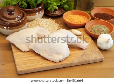 Raw chicken legs, spices and rice on a kitchen table. - stock photo