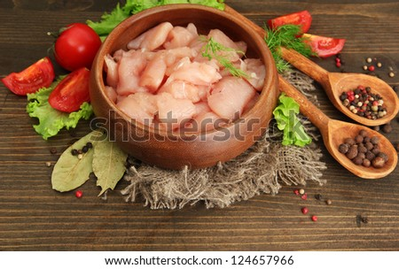 raw chicken meat in bowl, on wooden background - stock photo