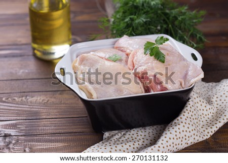 Raw chicken meat in bowl with herb  on dark painted wooden planks. Selective focus. Rustic style. - stock photo
