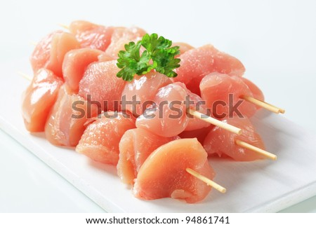 Raw chicken skewers on cutting board