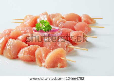 Raw chicken skewers on white background - stock photo