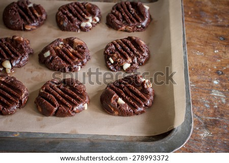 Raw chocolate cookie with hazelnut dough on a baking tray with parchment paper ready for bake - stock photo