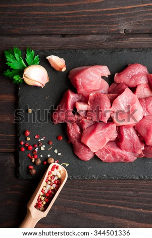 Raw chopped fresh meat with pepper and herbs over dark stone cutting board - stock photo