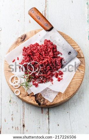 Raw chopped meat and meat cleaver on wooden cutting board on blue background - stock photo