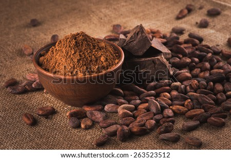 Raw cocoa beans, clay bowl  with cocoa powder, chocolate on sacking - stock photo