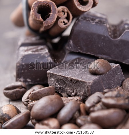 raw coffee beans and chocolate on old wooden plank - stock photo