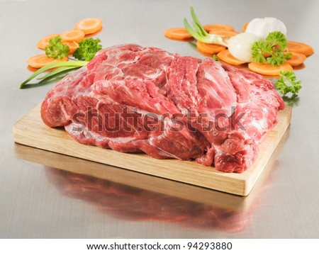 Raw collar butt on a cutting board and steel table - stock photo