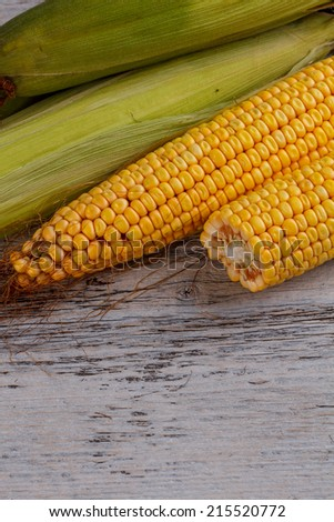Raw corn cobs on wooden background