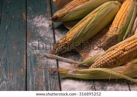 Raw corn cobs on wooden background close up