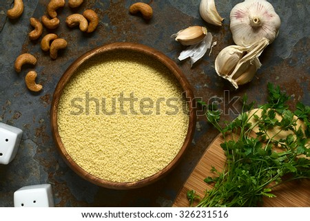 Raw couscous in wooden bowl, parsley, cashew nuts and garlic on the side, photographed overhead on slate with natural light - stock photo
