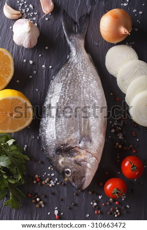 Raw dorado fish with ingredients on a table close-up. vertical top view - stock photo