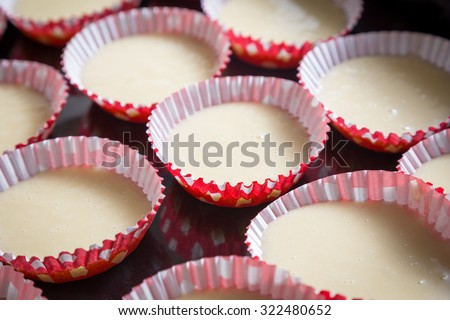 raw dough for cupcakes in the form on tray before bake - stock photo