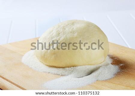 Raw dough on a kitchen board prepared for pizza - stock photo
