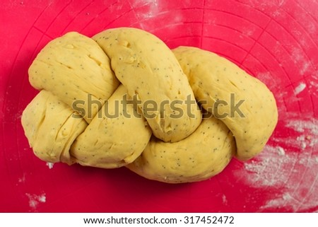 Raw dough rising on floured wooden surface. The preparations for baking fresh homemade breaded  bread - stock photo