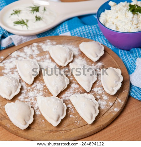raw dumplings with cottage cheese on a cutting board