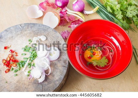 Raw egg in a red bowl and garnish - stock photo