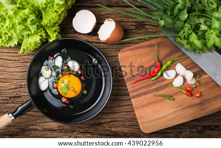 raw egg in pan and vegetable on wood background, prepared food for breakfast. - stock photo