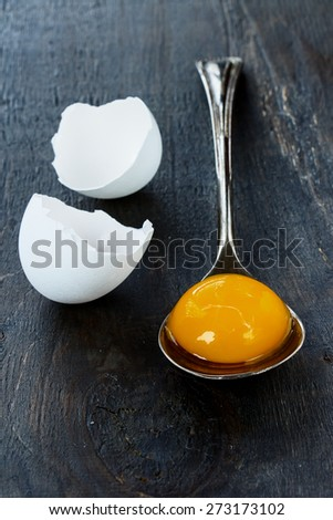 Raw egg on vintage spoon with eggshell over dark background. Selective focus. - stock photo